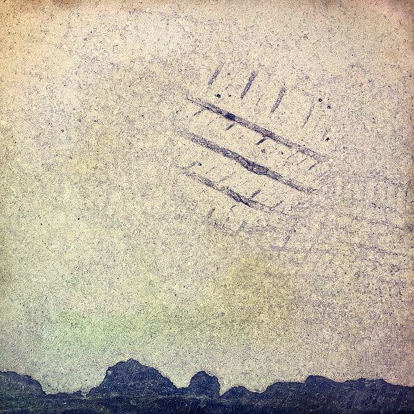 Výtvarná fotografie cyklus Krajiny imaginace. Silueta čených kopců na horizontu a na místě slunce otisk pneumatiky v rozehřátém asfaltu.