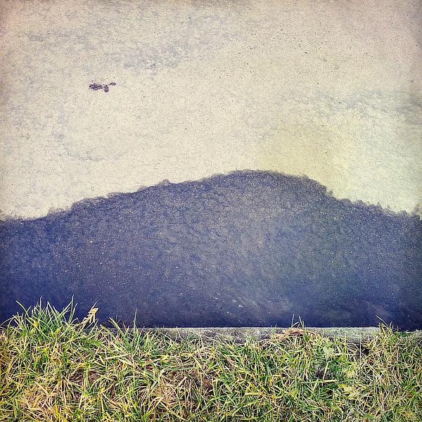 Výtvarná fotografie cyklus Krajiny imaginace. Kaluž vody a tráva na okraji chodníku připomíná louku a vzdálené hory.